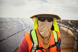 Woker At Solar Farm Looking Into Camera All Covered Up From the Sun